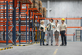 Description: Businesspeople and workers in warehouse